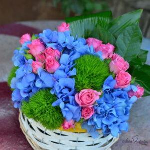Aranjament floral cu hortensie şi trandafiri în coş.