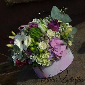 Aranjament de primăvară cu trandafiri, lisianthus, mini gerbera, lalele într-o cutie roz de carton.