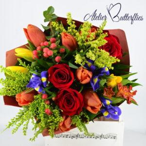 Buchet multicolor de primăvară cu trandafiri, lalele galbene şi portocalii, irişi.