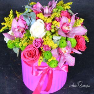 Aranjament cu trandafiri şi orhidee aşezate într-o cutie cilindrică roz.