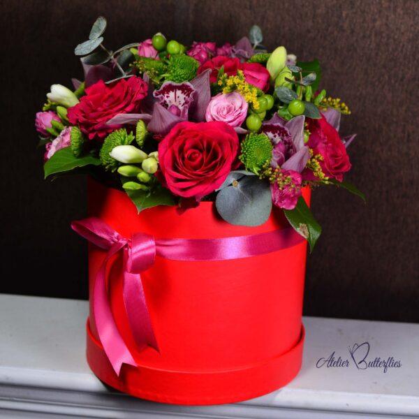 Aranjamentul floral cu trandafiri, orhidee, frezii, cymbidium într-o cutie de carton.